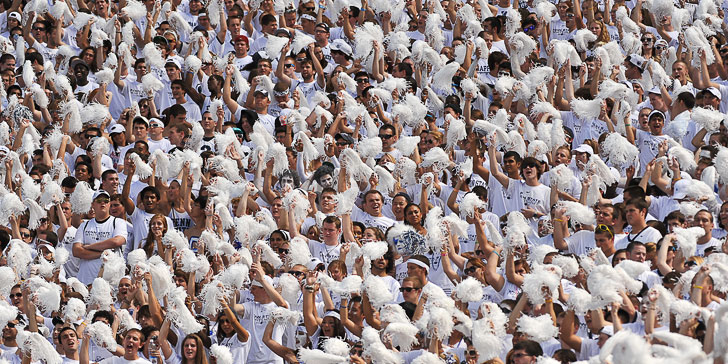 Image of a whiteout crowd cheering and waving pom poms